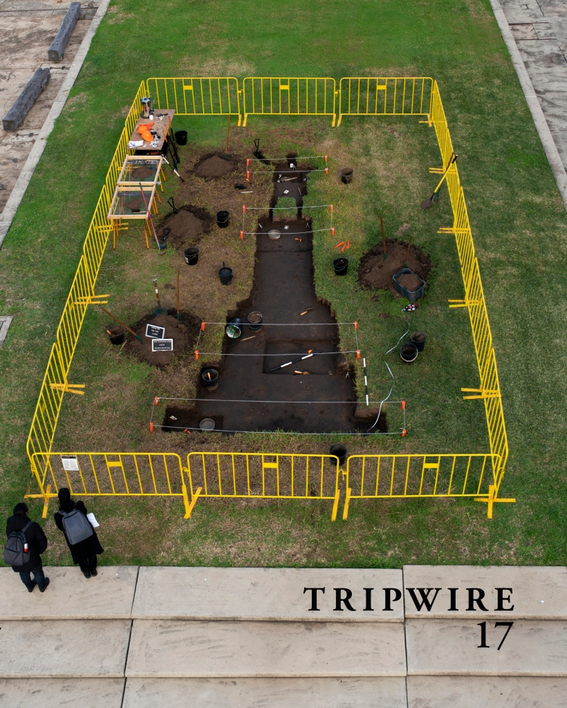 "Front cover of TRIPWIRE 17, featuring the journal name and number in the bottom right corner and a cover image which is a photo by Nicholas Galanin, ""Shadow on the land, an excavation and bush burial,"" earthworks, archaeological dig tools, barriers, 2020."